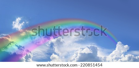 Wide blue sky with fluffy cloud formations clouds and a rainbow arcing off into the distance - stock photo