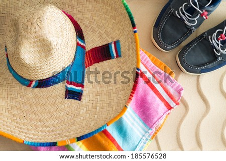 Wide brimmed straw sombrero lying on a colorful striped beach towel with a pair of sneakers on tropical beach sand with a decorative wavy pattern, view from above conceptual of summer holidays - stock photo