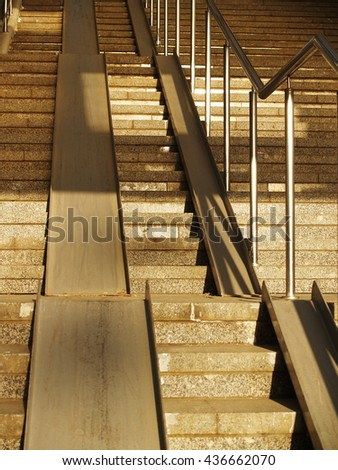 Wide concrete stairway with metallic ramp and railing - stock photo