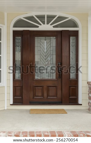 Wide Decorative Archway with Art Deco Front Door on Yellow House - stock photo