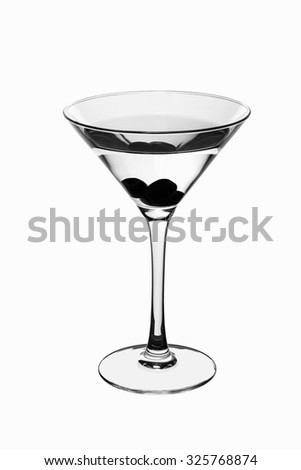 Wide glass on high legs with olives in a clear fluid. Wide glass on a high stem with three olives transparent liquid. Close-up on a white background. Black and white. - stock photo
