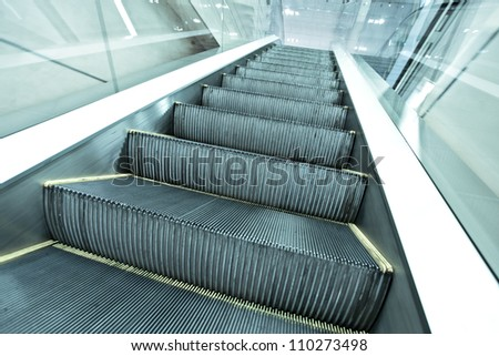 Wide long gray steps of quick moving escalator way in business passage, industrial motion background - stock photo