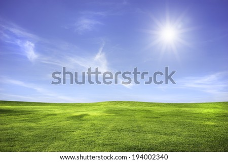 Wide meadow with clouds in blue sky in sunny day - stock photo