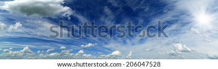 wide panorama of beautiful sky with clouds and sun - stock photo