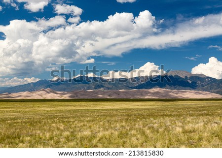 Wide panorama of the dunes at Great Sand Dunes National Park in Colorado with the mountains behind. Unusual to see clouds over the sand - stock photo