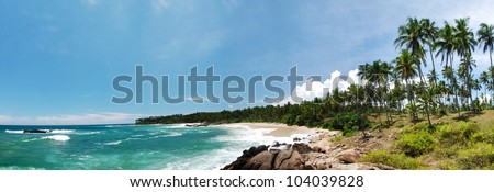 Wide panoramic photo of a tropical paradise on Sri Lanka with palms hanging over the beach and turquoise sea. - stock photo