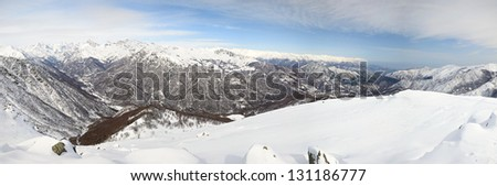 Wide panoramic view of alpine valley and high mountain peaks, in a winter scenery and cloudy day