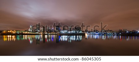 Wide Panoramic View of Montreal at night with color light reflection in water. - stock photo
