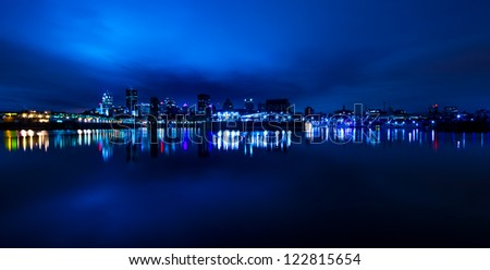 Wide Panoramic View of Montreal, with reflection light in the water, in blue tone at night. - stock photo
