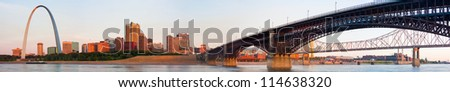 Wide panoramic view of St Louis downtown including the Arch and Eads Bridge train crossing spanning the Mississippi river - stock photo