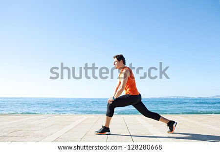 Wide profile view of a sports man figure stretching his legs on a track along the sea with the blue sky in the background and space around him. - stock photo