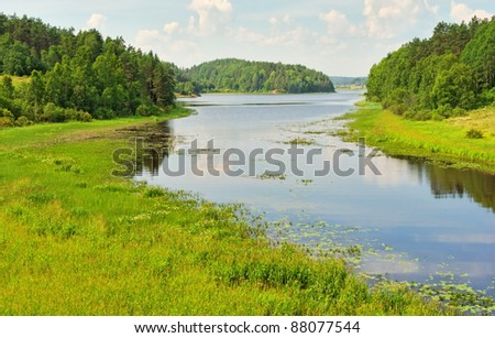 wide river in green banks overgrown with woods - stock photo