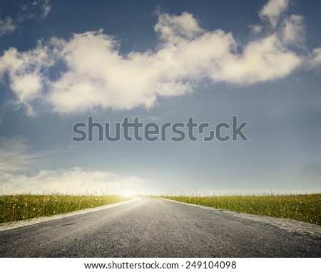 Wide road and green meadow at blue cloudy sky background  - stock photo