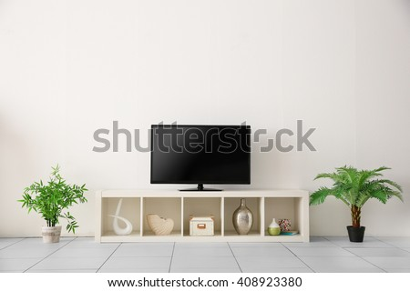 wide screen TV on white stand near light wall - stock photo