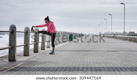 Wide shot landscape image of a mixed race female professional runner wearing a pink sweat shirt busy stretching her quads on a ocean side promenade railing - stock photo