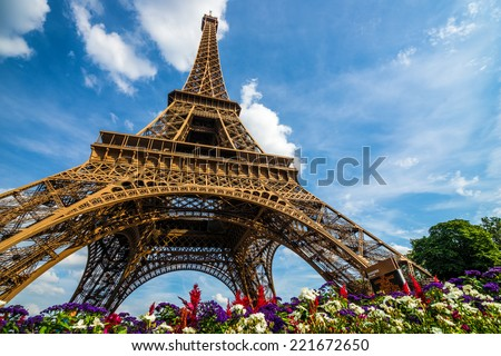 Wide shot of Eiffel Tower with dramatic sky and flowers at late evening, Paris, France - stock photo