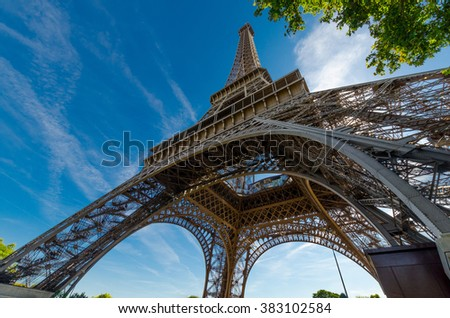 Wide shot of Eiffel Tower with dramatic sky and tree, Paris, France - stock photo