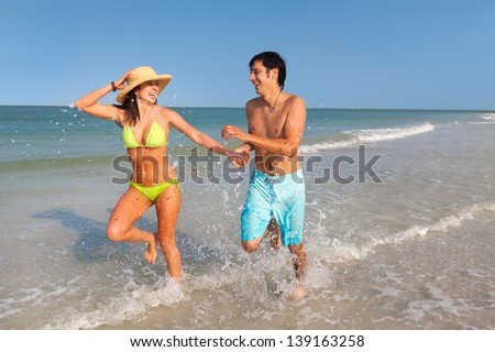 wide shot of Latin young Man and Woman running through surf on Florida Beach smiling - stock photo