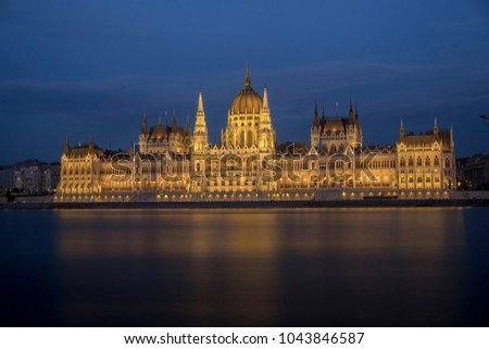 Wide  shot of the Hungarian parliament in Budapest during blue hour. The building is all lit up