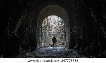Wide silhouette view of a lone survivor emerging from entrance or exit of an abandoned cave tunnel with an apocalyptic feel and dark cinematic grunge effect. - stock photo