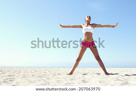Wide space view of an athletic african american attractive young woman exercising holding her arms and legs stretched out against a blue sky on a sunny beach. Sport and healthy lifestyle, outdoors. - stock photo