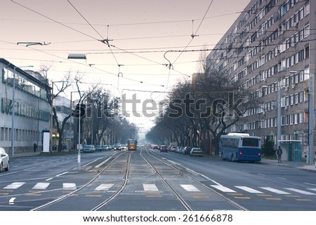 wide street with tram rails beside grey building blocks - stock photo