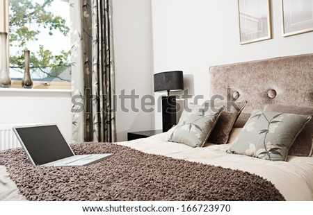 Wide view of a luxurious business hotel room with an open laptop on the textured blanket of an elegant and comfortable double bedroom with curtains, interior view. - stock photo