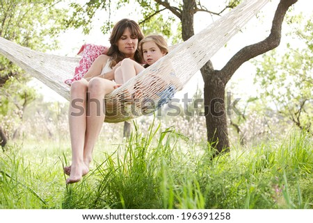 Wide view of a mother and daughter relaxing together being thoughtful sitting in a hammock, hugging and lounging during a sunny summer day in a holiday home garden with grass and trees, lifestyle. - stock photo