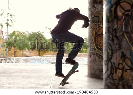 Wide view of a skillful skater silhouette jumping up and flicking his skateboard and doing challenging tricks with energy and dynamism in a skateboarding park, outdoors. Fun and sport lifestyle.
