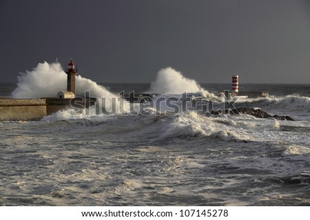 Wide view of a stormy sunset at the harbor of the mouth of the river Douro, in Porto, Portugal, with big waves against old lighthouse, new pier and beacon - stock photo