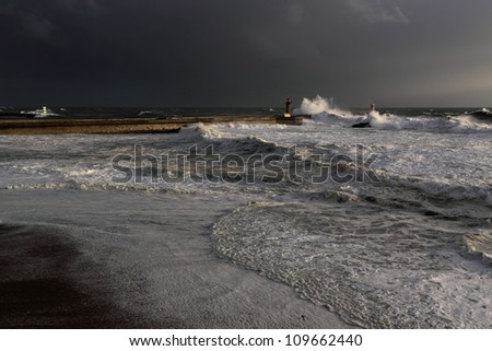 Wide view of a stormy sunset at the harbor of the mouth of the river Douro, in Porto, Portugal, with big waves against old lighthouse, new pier, beacons and seaside - stock photo