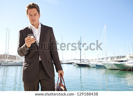 "Wide view of a stylish businessman using his ""smart phone"" while standing near a marine with luxury yachts against a deep blue sky and sea. - stock photo"