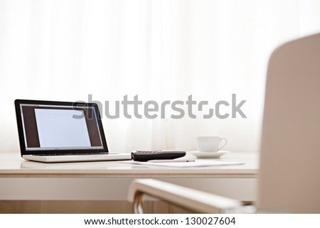 Wide view of a work desk interior with a laptop computer, a cup of coffee and white curtains on a sunny day. - stock photo