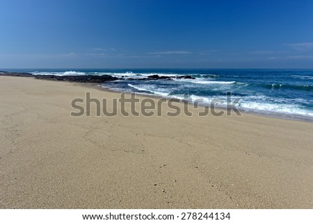 Wide view of an empty beach from the north of Portugal with deep blue sky  - stock photo