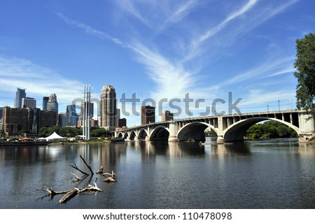 Wide view of downtown Minneapolis at left with Central Avenue (Minnesota 65) Bridge over Mississippi River - stock photo