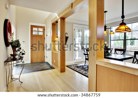 Wide view of home entrance and hallway with dining room in view - stock photo
