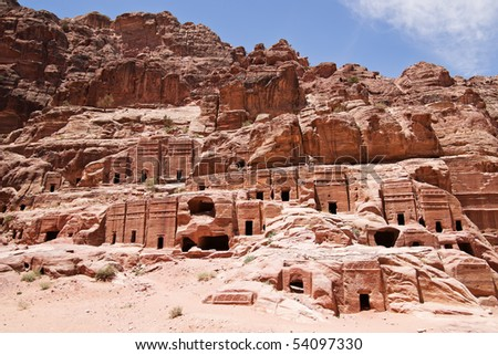 Wide view of large cliff side tomb carved from the beautiful richly-colored sandstone in the ancient city of Petra, Jordan - stock photo