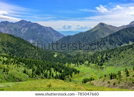 Wide view of mountain valley with rare forest and green alpine meadows. Tunkinsky National Park. Eastern Sayan. Russia