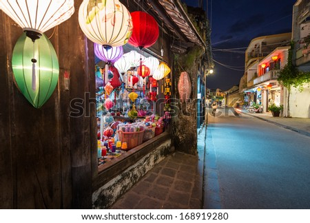 Wide view on narrow street in Hoi An town in Vietnam and shop on left with big bright window and multicolored lanterns over it. Houses going into distance on right. Travelling and tourism. - stock photo