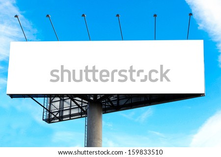 Wide white background of illuminated big blank billboard over cloudy blue sky with sparse clouds - stock photo