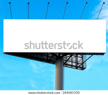Wide white background of illuminated big blank billboard over cloudy bright blue sky in sunny day. Successful concept of promotion products and items outdoor. Clear space of empty board for your text  - stock photo
