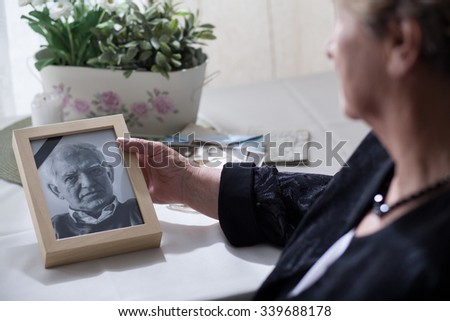 Widow looking at the photo of her dead husband - stock photo
