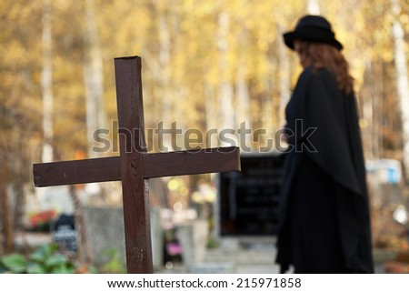 Widow standing between cross and husband's grave and suffering - stock photo