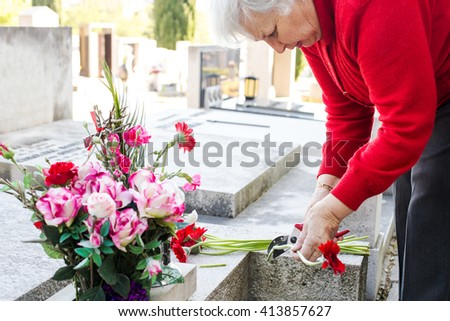 widow taking care ot the grave at cemetery