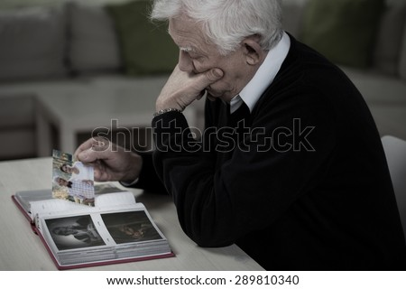 Widower looking at the photos and remembering deceased wife - stock photo