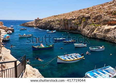 Wied Zurrieq Fjord, MALTA - JULY 24, 2015:  Maltese boats and swimming people in water  near Blue Grotto on south end of Malta island