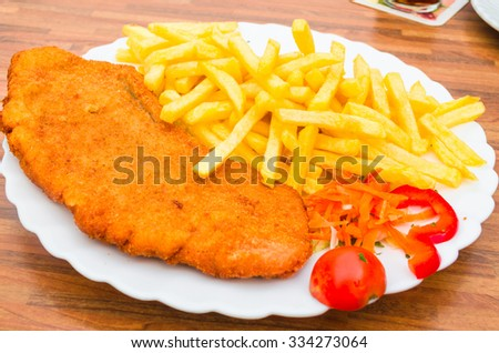 Wiener schnitzel, breaded steak with French fries and lemon - stock photo