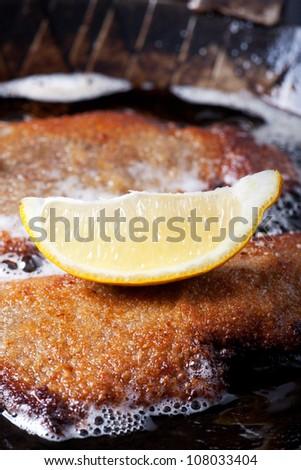 wiener schnitzel in an iron pan - stock photo