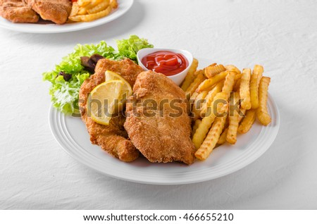 Wiener schnitzel with french fries, salad and a sharp dip