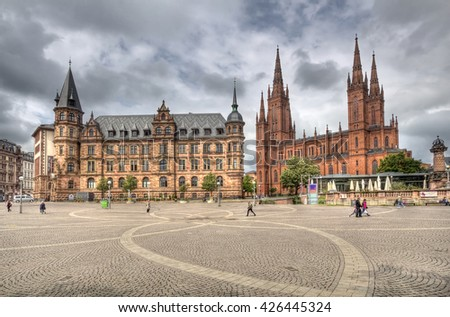Wiesbaden, Germany - April 29, 2014: People walk on the Demsches Gelande square in front of the new townhall and the  Marktkirche church in Wiesbaden, Germany on April 29, 2014 - stock photo